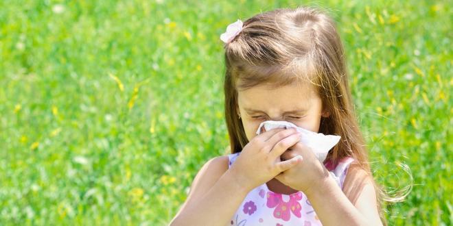 a girl sneezing in a summery field